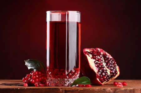 pomergranate: ripe pomergranate and glass of juice on wooden table on red background