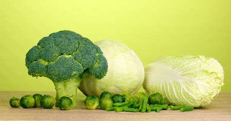 Fresh broccoli and cabbages on wooden table on green background Stock Photo - 12717650
