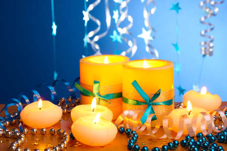 Beautiful candles, gifts and decor on wooden table on blue background Stock Photo - 12717591