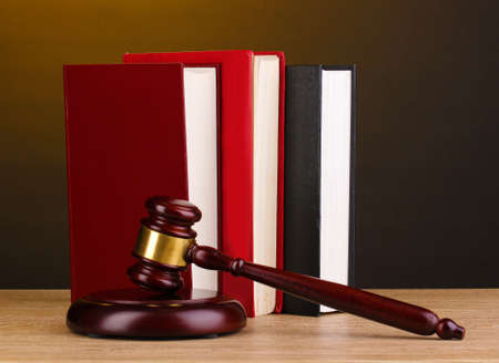 Judge's gavel and books on wooden table on brown background photo