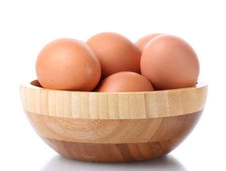 brown eggs in wooden bowl isolated on white photo