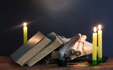 old books, scrolls, feather pen inkwell and candles on wooden table on blue background photo