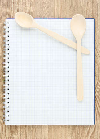 Open cookbook and kitchenware on wooden background photo