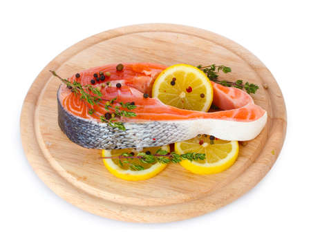 Red fish with lemon and thyme on wooden cutting board isolated on white  photo