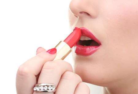 beautiful woman is applying her lips with red lipstick photo