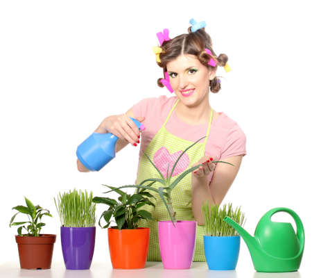 beautiful happy young housewife sprays plants in flowerpots isolated on white photo