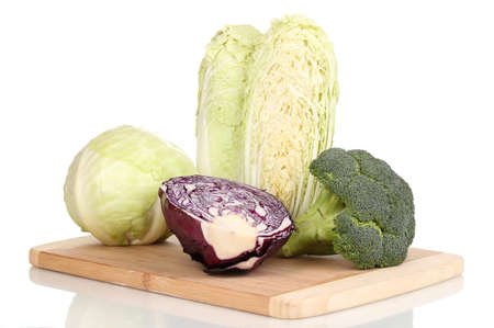 Cabbages and broccoli on wooden chopping board isolated on white