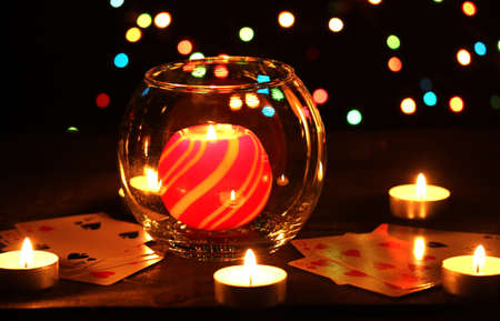 Candles and playing cards on wooden table on bright background photo