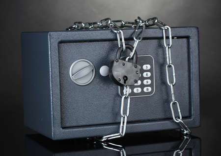 safe with chain and lock on grey background photo