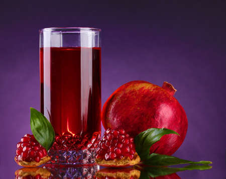 ripe pomergranate and glass of juice on purple background photo