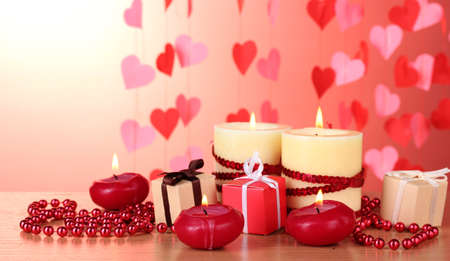 Beautiful candles with romantic decor on a wooden table on a red background Stock Photo - 12715902