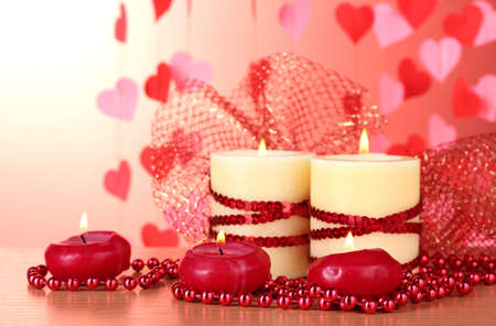 Beautiful candles with romantic decor on a wooden table on a red background Stock Photo - 12715825