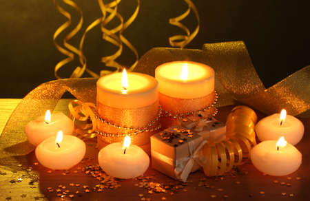 Beautiful candles, gifts and decor on wooden table on yellow background photo