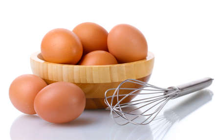 Metal whisk for whipping eggs and brown eggs in wooden bowl isolated on white Stock Photo - 12715940