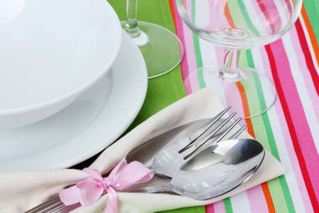 Table setting with fork, spoon, knife, plates, and napkin photo