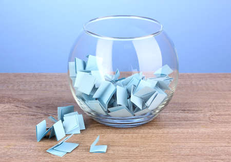 Pieces of paper for lottery in vase on wooden table on blue background photo