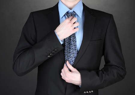 stropdas: zakenman het corrigeren van een das op zwarte achtergrond Stockfoto