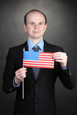 Businessman holding American flag on black background photo