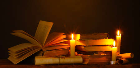 history books: Pile of old books with candle and scroll in dark