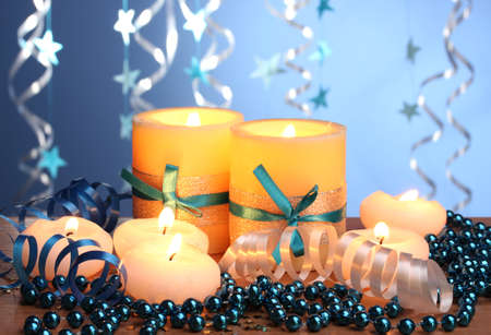 Beautiful candles, gifts and decor on wooden table on blue background Stock Photo - 12801149