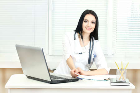 beautiful girl doctor in the office holding prescription photo