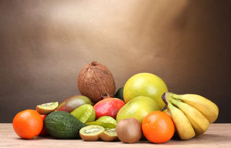 Assortment of exotic fruits on wooden table on brown background Stock Photo - 12800942