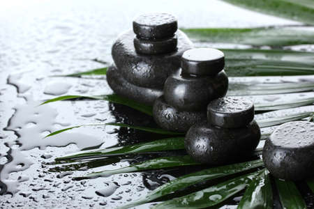 Spa stones with drops on green palm leaf on grey background photo