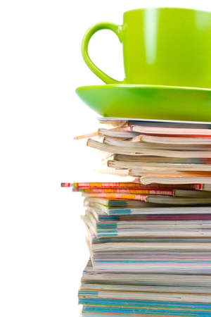 stack of magazines and cup isolated on white photo