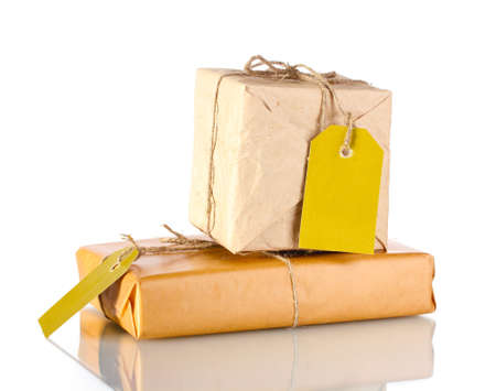 Two parcels wrapped in brown paper tied with twine and with blank labels isolated on white photo