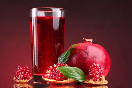 pomergranate: ripe pomergranate and glass of juice on red background Stock Photo