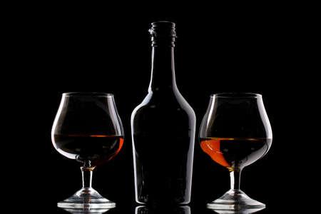 whisky bottle: Glasses of brandy and bottle on black background Stock Photo