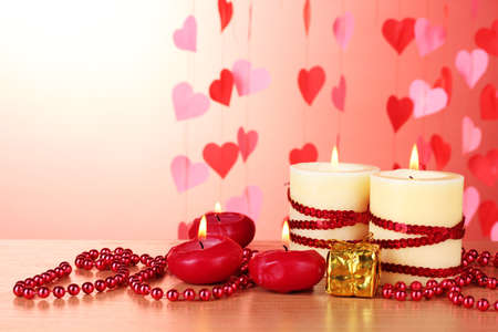 Beautiful candles with romantic decor on a wooden table on a red background Stock Photo - 12800493