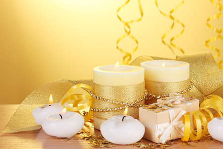 Beautiful candles, gifts and decor on wooden table on yellow background Stock Photo - 12800471