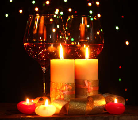 Beautiful candle and glasses of wine on wooden table on bright background photo