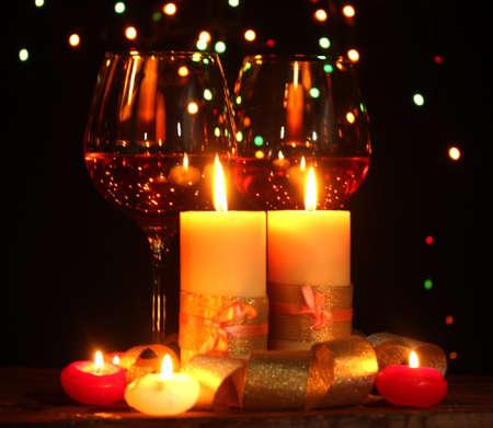 luz de velas: Vela Hermoso y copas de vino en la mesa de madera sobre fondo brillante