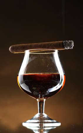 glass of brandy and cigar on brown background Stock Photo - 12800559