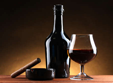 whisky bottle: bottle and glass of brandy and cigar on wooden table on brown background