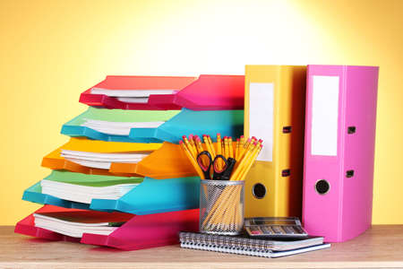 bright paper trays and stationery on wooden table on yellow background photo
