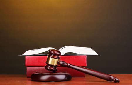 Judge's gavel and books on wooden table on brown background Stock Photo - 12799623