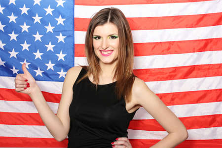 beautiful young woman with the American flag on the background photo