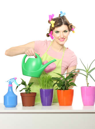beautiful happy young housewife watering plants in flowerpots isolated on white photo