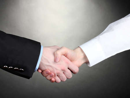 negotiating: Business handshake on gray background