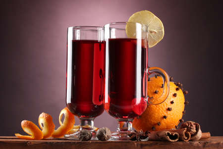 mulled wine in the glasses, spice and orange on wooden table on purple background photo