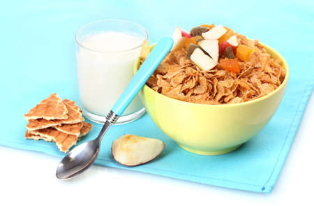 tasty cornflakes in bowl with dried fruits and glass of milk on blue napkin photo