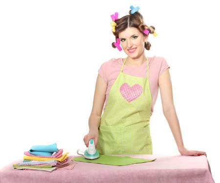 beautiful young housewife with iron and  pile of clothes isolated on white photo