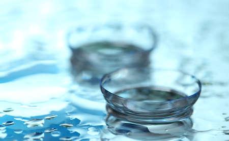 contact lenses: lentes de contacto con las gotas sobre fondo azul Foto de archivo