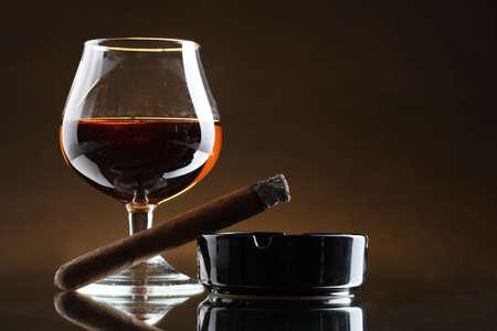 glas cognac en sigaar op bruine achtergrond