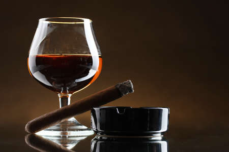glass of brandy and cigar on brown background Stock Photo - 12822756