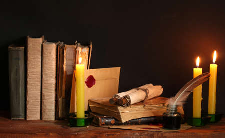 ged: old books, scrolls, feather pen inkwell and candles on wooden table on brown background
