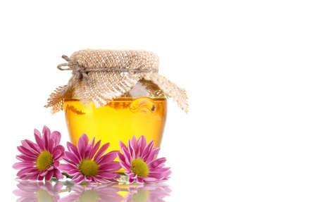 Sweet honey in jar isolated on white photo